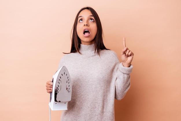 Mulher jovem de raça mista segurando um ferro isolado apontando para cima com a boca aberta.