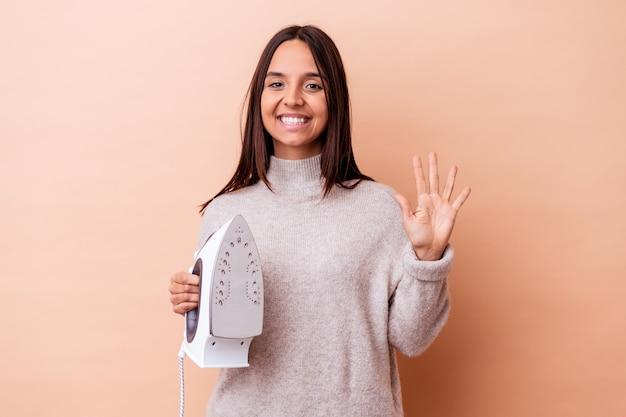Mulher jovem de raça mista segurando um ferro isolado sorrindo alegre mostrando o número cinco com os dedos.