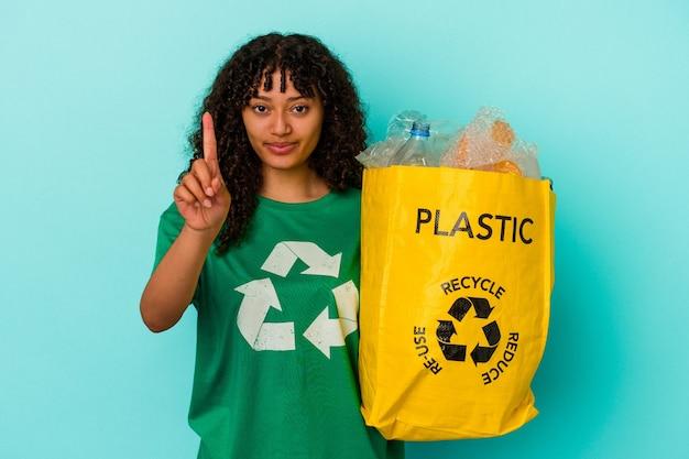 Mulher jovem de raça mista segurando um saco plástico reciclado isolado em um fundo azul, mostrando o número um com o dedo.