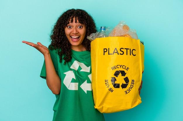 Mulher jovem de raça mista segurando um saco plástico reciclado isolado em um fundo azul, recebendo uma agradável surpresa, animada e levantando as mãos.