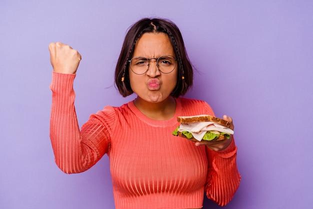Mulher jovem de raça mista segurando um sanduíche isolado no fundo roxo, mostrando o punho para a câmera, expressão facial agressiva.
