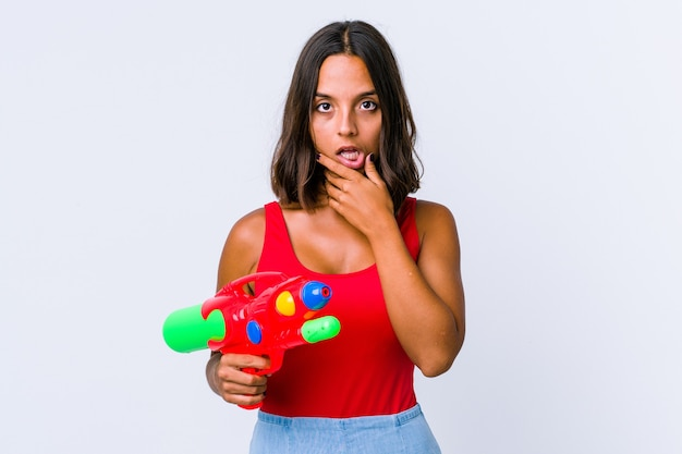 Mulher jovem de raça mista segurando uma arma de água isolada detém o espaço da cópia na palma da mão, manter a mão na bochecha. espantado e encantado.
