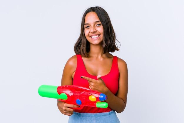 Mulher jovem de raça mista segurando uma pistola de água isolada animado segurando um espaço de cópia na palma da mão.