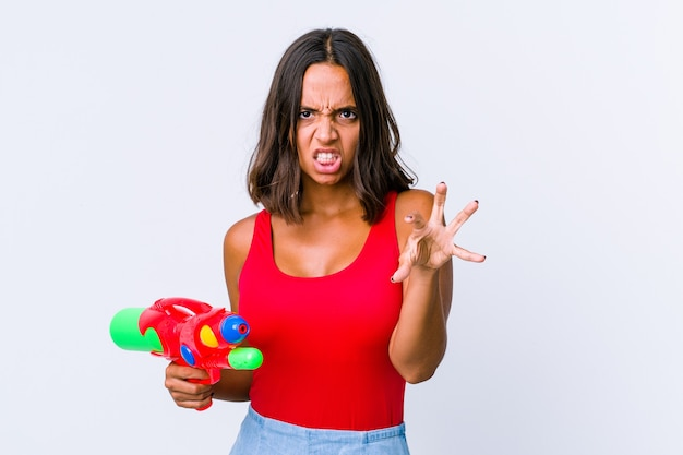Mulher jovem de raça mista segurando uma pistola de água isolada mostrando garras imitando um gato, gesto agressivo.