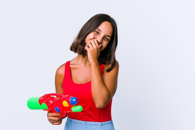 Mulher jovem de raça mista segurando uma pistola de água isolada, rindo de emoção feliz, despreocupada e natural.