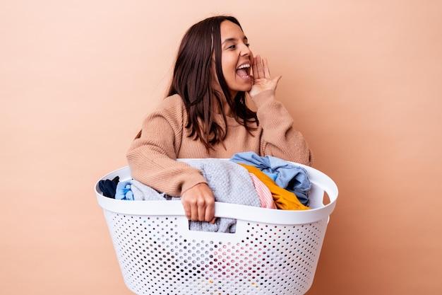 Mulher jovem de raça mista segurando uma roupa isolada gritando e segurando a palma da mão perto da boca aberta.
