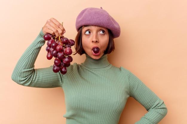 Mulher jovem de raça mista segurando uvas isoladas em uma parede bege