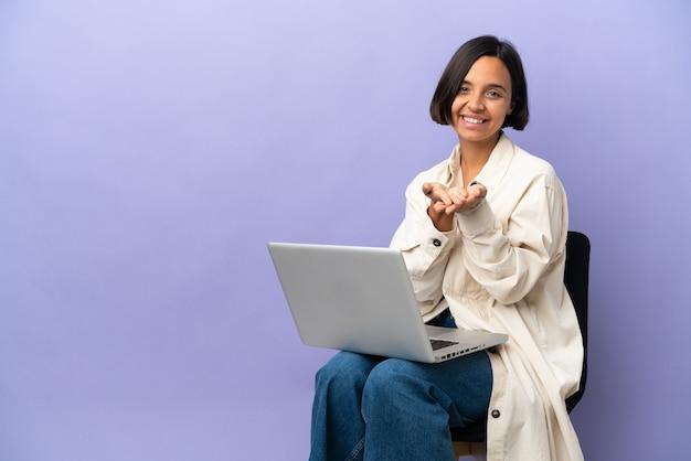 Mulher jovem de raça mista sentada em uma cadeira com laptop isolado em um fundo roxo segurando copyspace imaginário na palma para inserir um anúncio