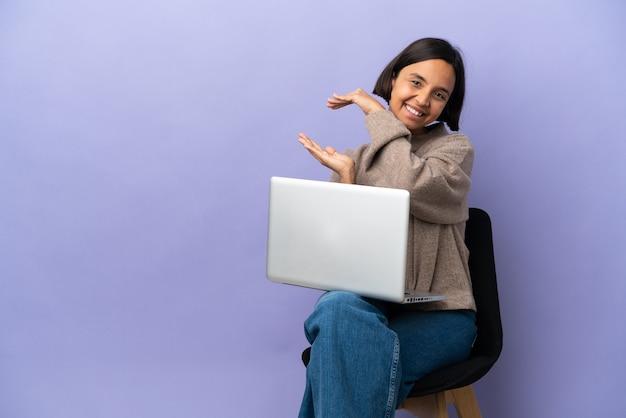 Mulher jovem de raça mista sentada em uma cadeira com laptop isolado em um fundo roxo segurando copyspace para inserir um anúncio