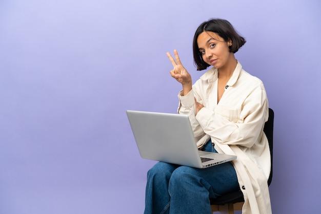 Mulher jovem de raça mista sentada em uma cadeira com laptop isolado em um fundo roxo sorrindo e mostrando sinal de vitória