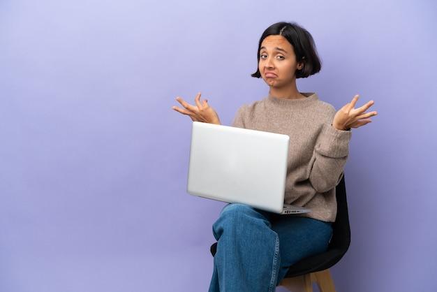 Mulher jovem de raça mista sentada em uma cadeira com laptop isolado em um fundo roxo tendo dúvidas