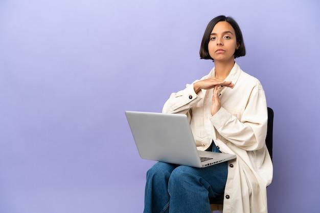 Mulher jovem de raça mista sentada em uma cadeira com laptop isolado no fundo roxo fazendo gesto de castigo