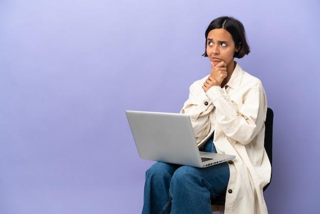 Mulher jovem de raça mista sentada em uma cadeira com laptop isolado no fundo roxo, tendo dúvidas e com expressão facial confusa