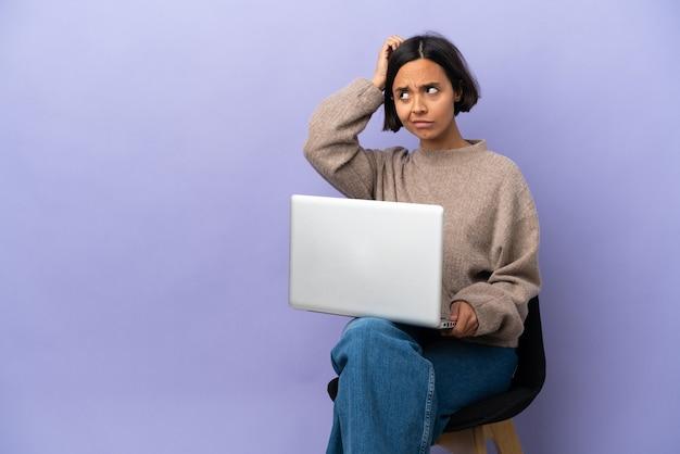 Mulher jovem de raça mista sentada em uma cadeira com laptop isolado no fundo roxo tendo dúvidas enquanto coça a cabeça