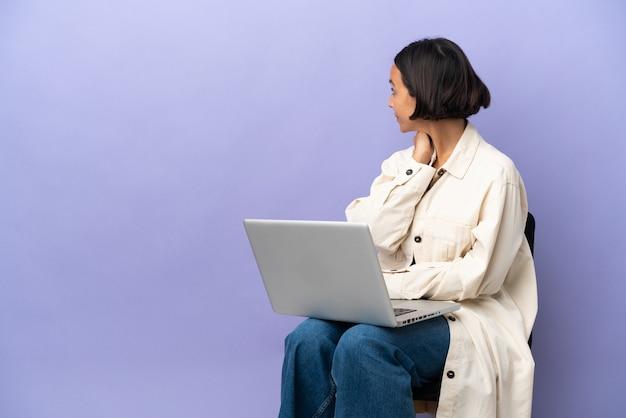 Mulher jovem de raça mista sentada em uma cadeira com o laptop isolado em um fundo roxo na posição traseira e pensando