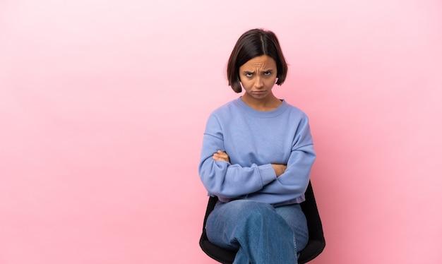 Mulher jovem de raça mista sentada em uma cadeira isolada em um fundo rosa com uma expressão triste