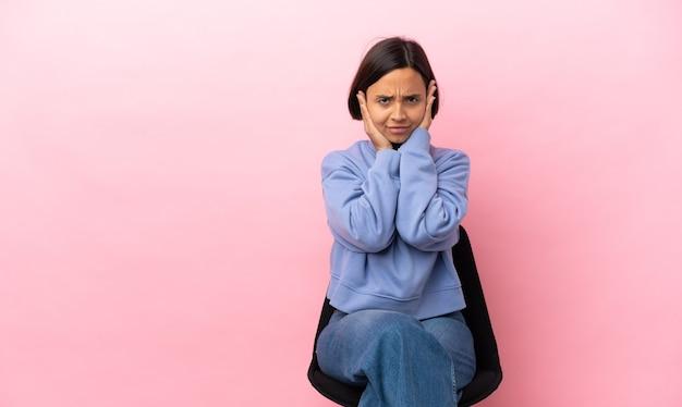 Mulher jovem de raça mista sentada em uma cadeira isolada em um fundo rosa frustrada e cobrindo as orelhas