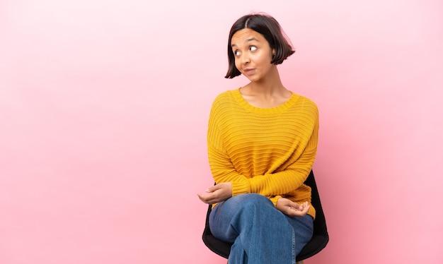 Mulher jovem de raça mista sentada em uma cadeira isolada em um fundo rosa tendo dúvidas enquanto olha de lado