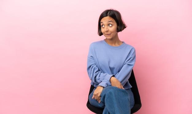 Mulher jovem de raça mista sentada em uma cadeira isolada em um fundo rosa tendo dúvidas enquanto olha para cima