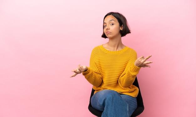 Mulher jovem de raça mista sentada em uma cadeira isolada em um fundo rosa tendo dúvidas