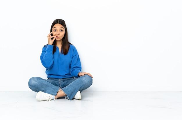 Mulher jovem de raça mista, sentada no chão isolado no branco, mostrando um sinal de gesto de silêncio
