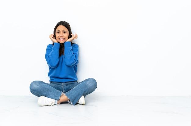 Mulher jovem de raça mista, sentada no chão isolado no espaço em branco, frustrado e cobrindo as orelhas