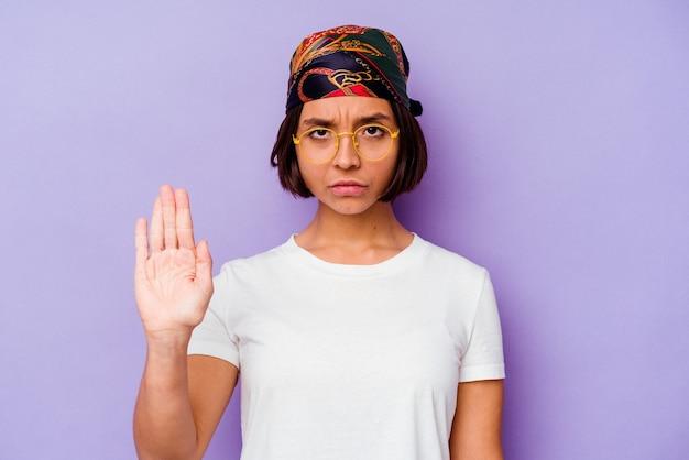 Mulher jovem de raça mista usando uma bandana isolada em um fundo roxo em pé com a mão estendida, mostrando o sinal de pare, impedindo-o.
