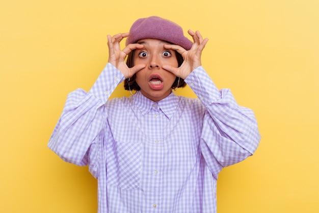 Mulher jovem de raça mista usando uma boina isolada na parede amarela, mantendo os olhos abertos para encontrar uma oportunidade de sucesso.