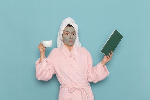 Mulher jovem de roupão rosa após o banho, bebendo café na parede azul, beleza, limpeza, água limpa, creme, autocuidado