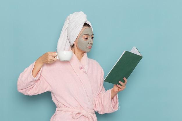 Mulher jovem de roupão rosa bebendo café e lendo o caderno na mesa azul. limpeza