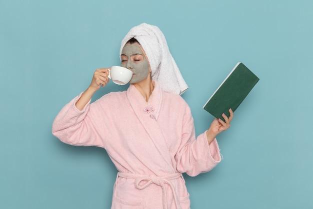 Mulher jovem de roupão rosa bebendo café e lendo um caderno na parede azul. limpeza