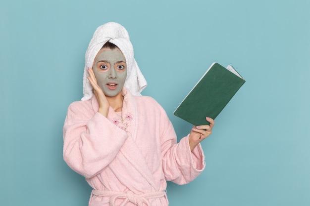 Mulher jovem de roupão rosa segurando e lendo o caderno na parede azul beleza banho de água creme banho de chuveiro