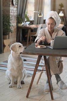 Mulher jovem de roupão sentada à mesa em frente ao laptop e bebendo café com um cachorro sentado perto dela em casa