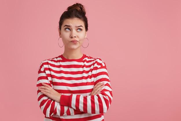 Mulher jovem de sardas, infeliz, escuta alguém com tristeza, chateada, em pé com os braços cruzados, vestida de lenha listrada viva, carrancuda e olhando para cima, isolada sobre parede rosa