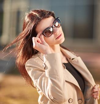 Mulher jovem de sucesso em pé na rua num dia de outono