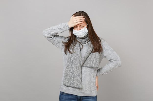 Mulher jovem de suéter cinza e lenço com máscara facial estéril, mantendo os olhos fechados, colocou a mão na testa isolada no fundo cinza. estilo de vida saudável, tratamento de doença doente, conceito de estação fria.