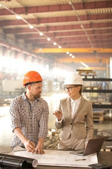 Mulher jovem de terno e capacete explicando seu ponto de vista sobre o novo projeto em conversa com um colega na reunião