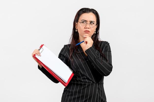 Mulher jovem de terno escuro com uma caneta e um documento no fundo branco.