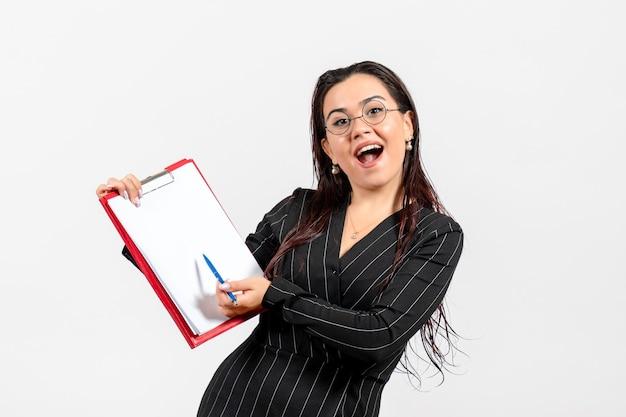 Mulher jovem de terno escuro de frente e verso segurando um documento e uma caneta sobre fundo branco claro.