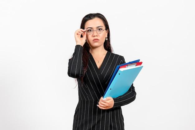Mulher jovem de terno escuro segurando documentos sobre fundo branco documento de trabalho de escritório feminino de frente