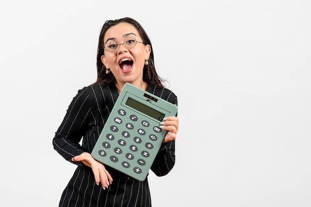 Mulher jovem de terno escuro segurando uma calculadora grande no fundo branco.