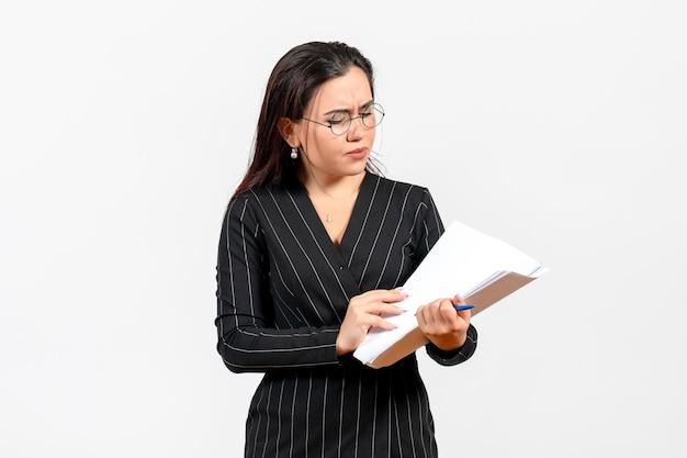Mulher jovem de terno escuro, vista frontal, segurando e verificando arquivos no fundo branco documento feminino trabalho de escritório de negócios