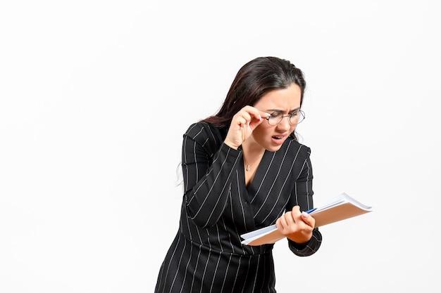 Mulher jovem de terno escuro, vista frontal, segurando e verificando arquivos no trabalho de escritório de negócios de documento feminino de fundo branco