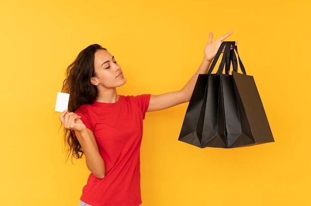 Mulher jovem de vendas detém sacolas pretas e cartão de crédito.