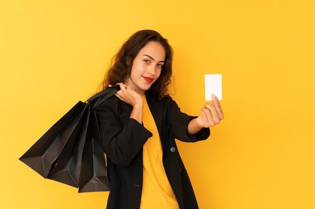 Mulher jovem de vendas segura sacolas de compras pretas e cartão de crédito, usa uma jaqueta preta.