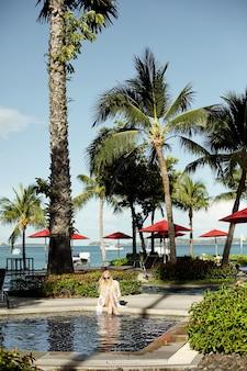 Mulher jovem de vestido branco e biquíni relaxa na piscina ao ar livre sob palmeiras exóticas ...
