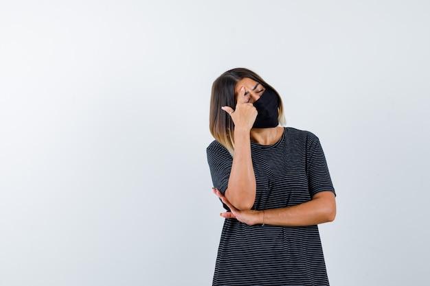 Mulher jovem de vestido preto, máscara preta colocando o dedo indicador na testa, segurando uma mão sob o cotovelo e parecendo exausta, vista frontal.