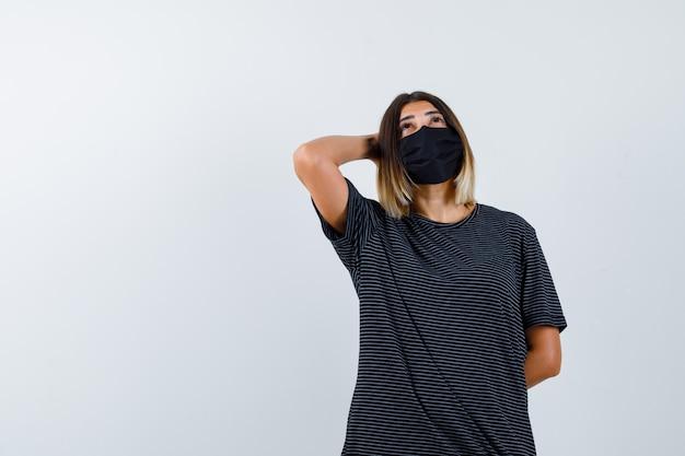 Mulher jovem de vestido preto, máscara preta colocando uma mão atrás da cabeça, a outra mão atrás da cintura, olhando para cima e olhando pensativa, vista frontal.