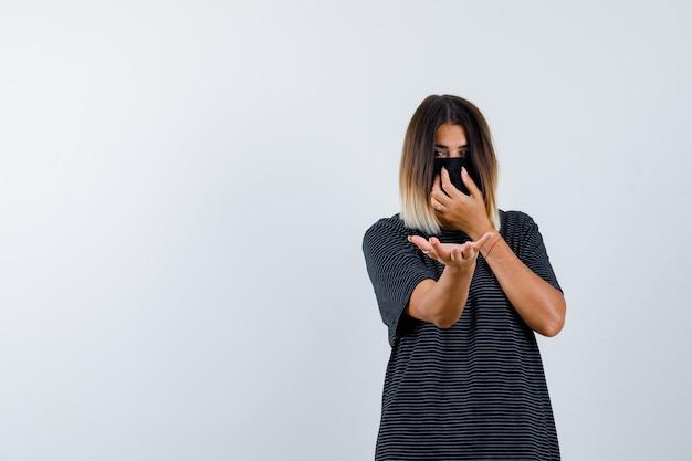 Mulher jovem de vestido preto, máscara preta esticando uma mão em direção à câmera segurando algo, colocando a outra mão na máscara e olhando séria, vista frontal.