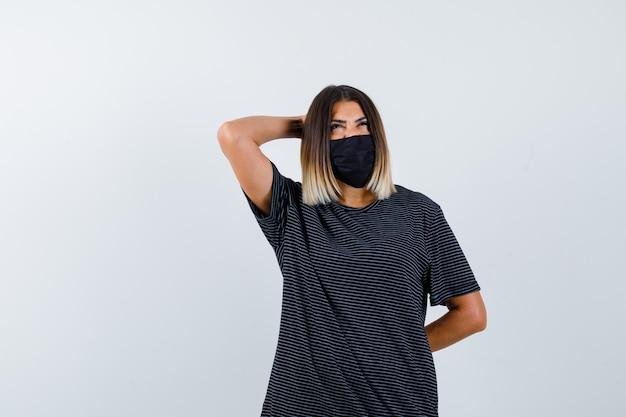 Mulher jovem de vestido preto, máscara preta, segurando uma mão atrás da cabeça, a outra atrás da cintura, olhando para cima e olhando pensativa, vista frontal.
